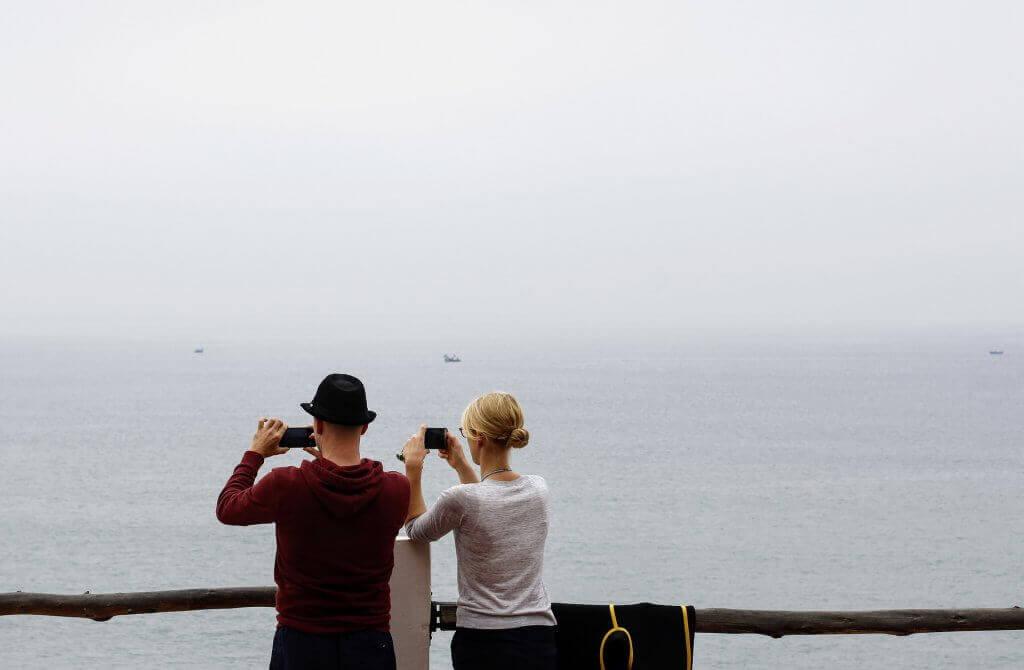 Casal tirando fotos do mar