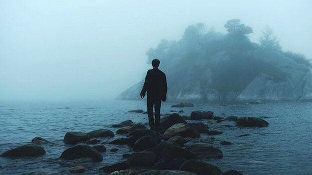 Homem andando sob rochas no mar