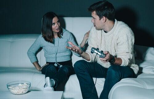 Homem jogando videogame com a mulher reclamando