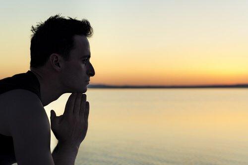 Homem pensando em sua vida no por do sol