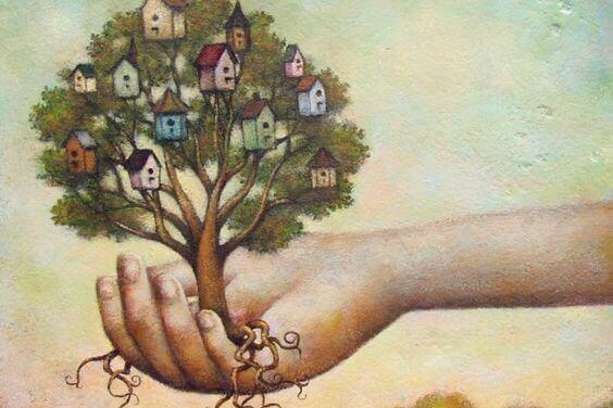 Mão segurando árvore com casas nos galhos