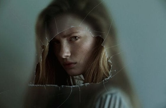 Menina atrás de vidro quebrado