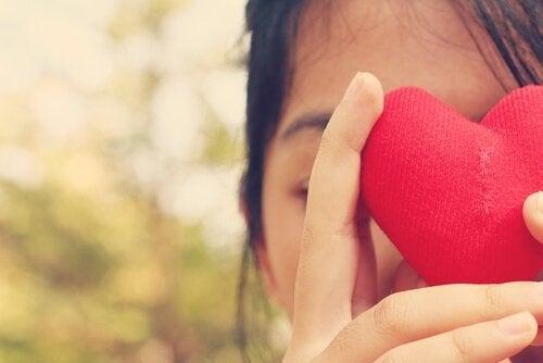 Mulher segurando coração vermelho