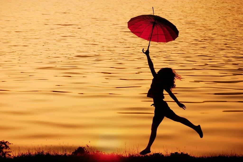 Mulher pulando com sombrinha