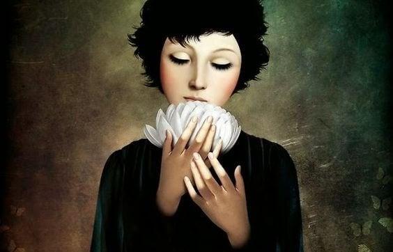 Mulher com flor branca nas mãos