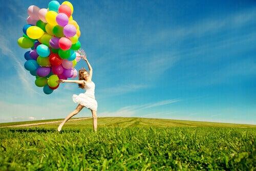Mulher feliz carregando balões coloridos