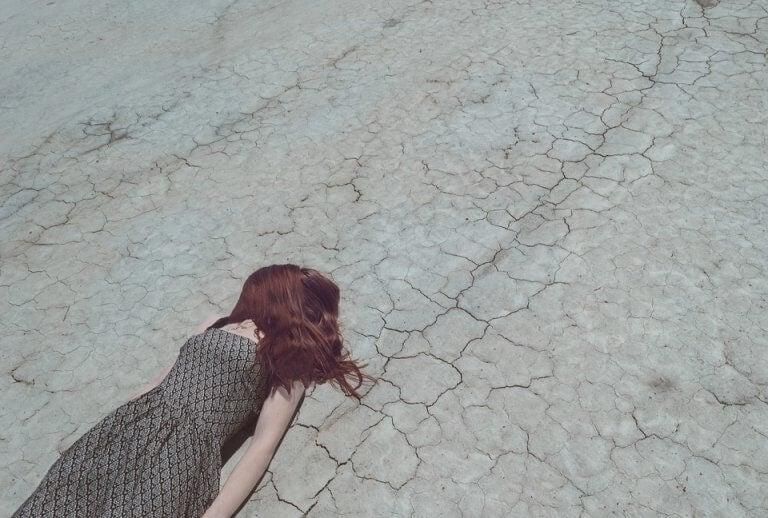 Mulher deitada em chão árido e seco