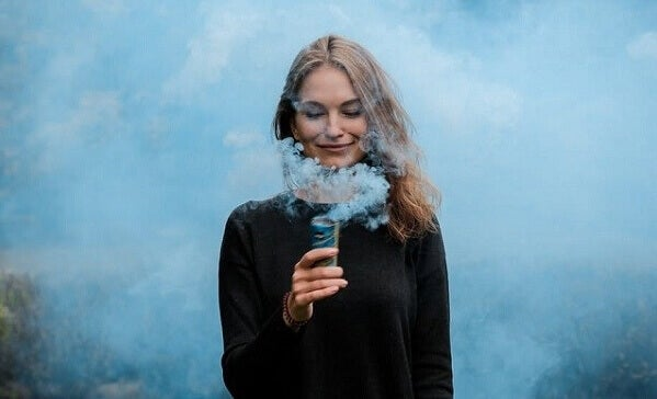 Mulher feliz observando fumaça azul