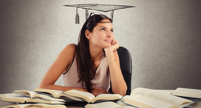 Mulher estudando e pensando em quando se formar