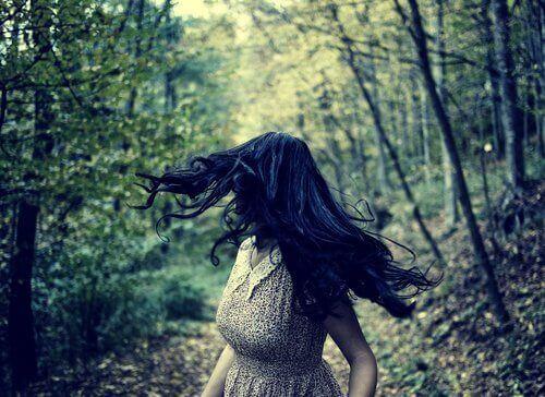 Mulher com medo correndo de ameaça em floresta