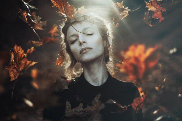 Mulher envolta por folhas de outono