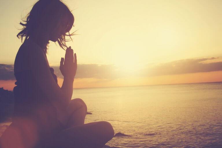 Mulher meditando no por do sol