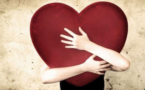 Pessoa abraçando coração vermelho
