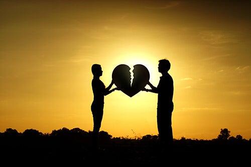 Homem e mulher segurando coração partido