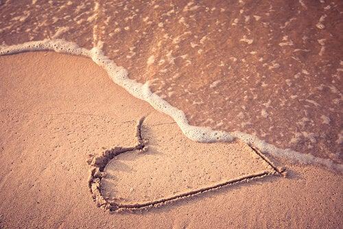 Onda apagando coração desenhado na areia
