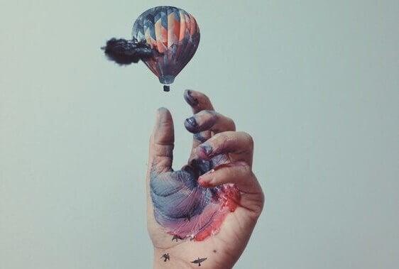 Mão com tinta tentando pegar balão
