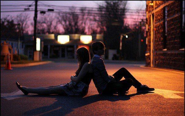 Casal sentado de costas no meio da rua
