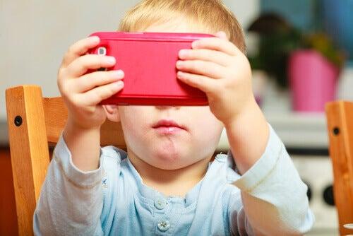 Criança pequena mexendo em celular