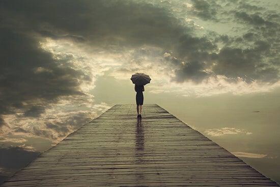 Mulher caminhando em ponte com guarda-chuva
