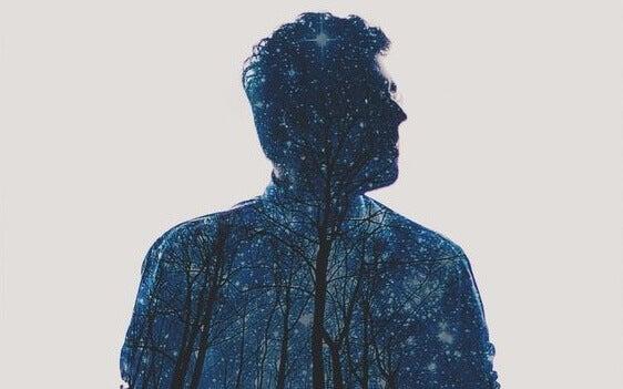 Corpo de homem com floresta e céu estrelado