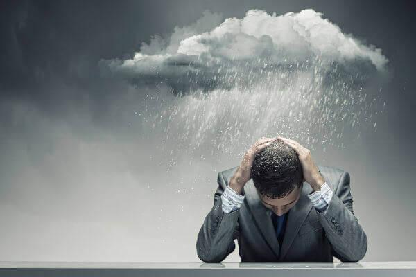 Homem sob uma nuvem de chuva
