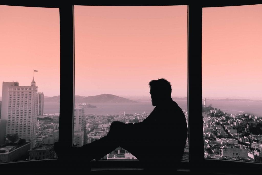 Homem olhando pela janela ao entardecer