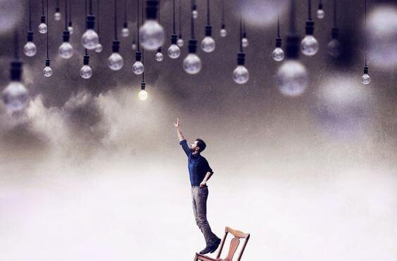 Homem tentando alcançar lâmpada acesa