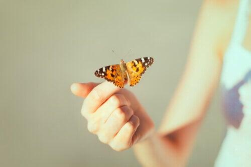 Mulher com borboleta em sua mão