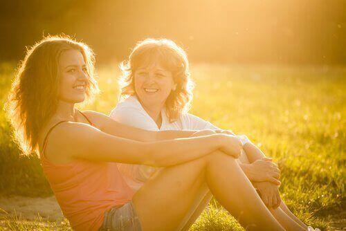Mãe e filha no campo sob o sol