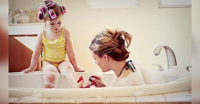 Mãe na banheira com sua filha