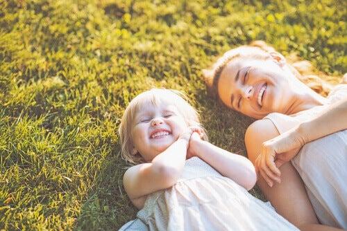 Mãe rindo com sua filha deitadas na grama