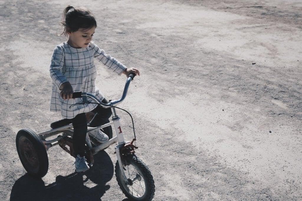 Menina andando de triciclo