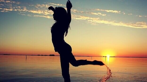 Mulher dançando diante do por do sol