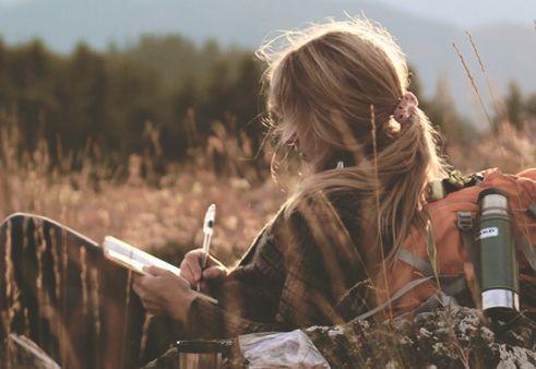 Menina escrevendo carta no campo