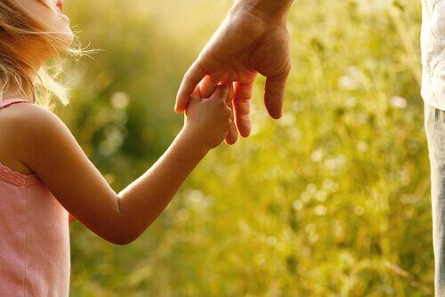 Menina segurando a mão de seu pai