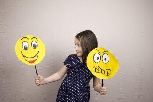 Menina segurando rostos desenhados