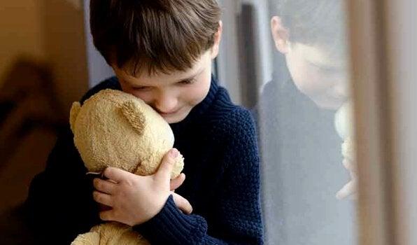 Menino abraçando seu ursinho de pelúcia