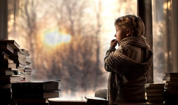 Menino em casa observando livros