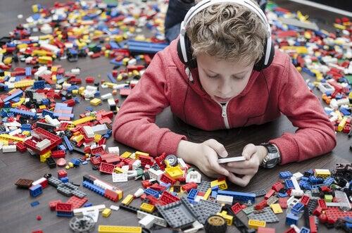 Menino brincando no celular com legos em volta