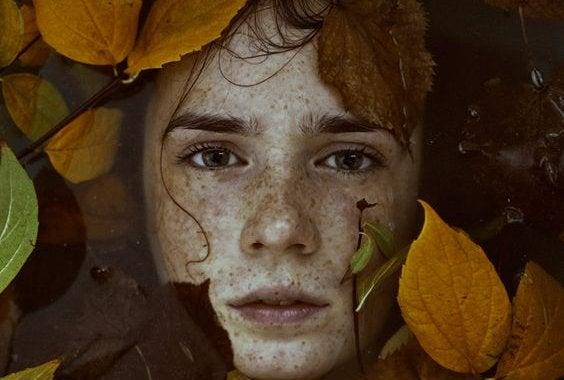 Rosto rodeado por folhas de outono