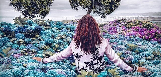 Mulher caminhando em jardim de flores