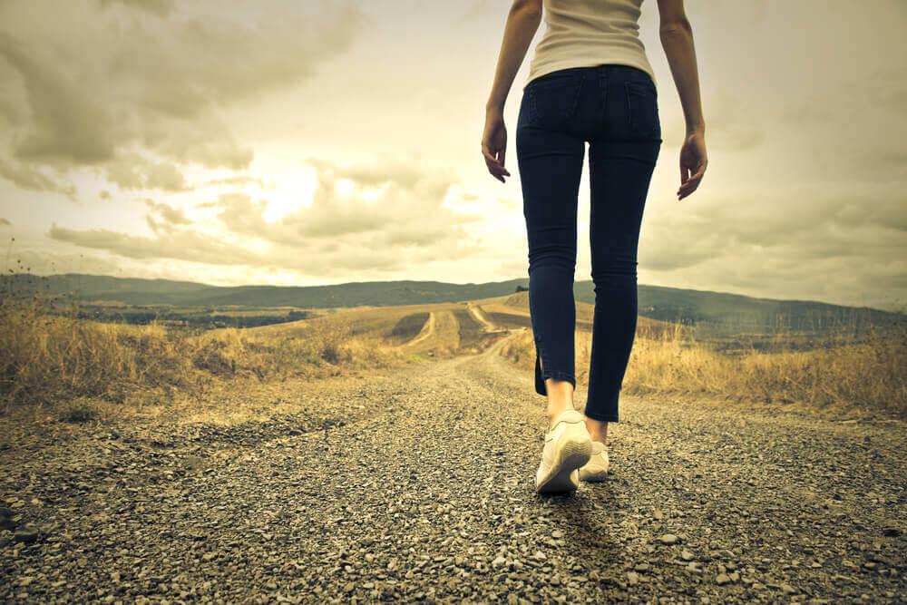 Mulher caminhando em estrada vazia
