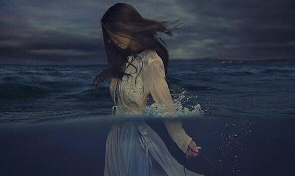 Mulher caminhando no mar