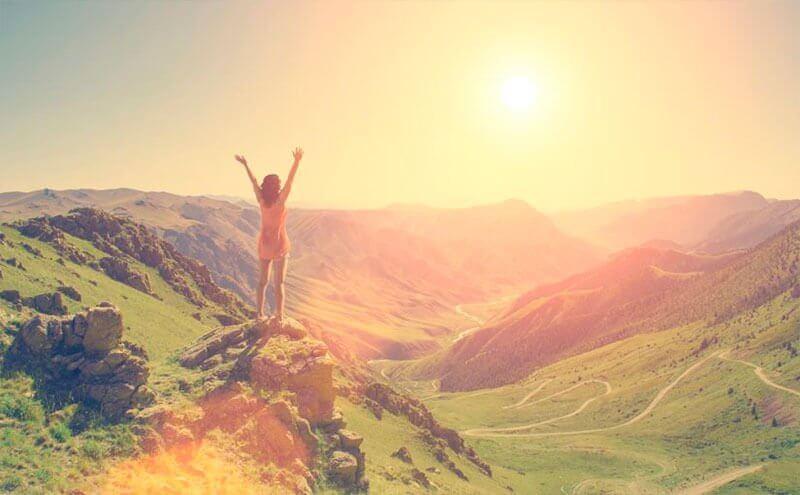 Mulher feliz por chegar ao topo da montanha