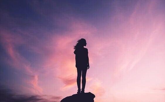 Mulher em cima de pedra desfrutando o por do sol