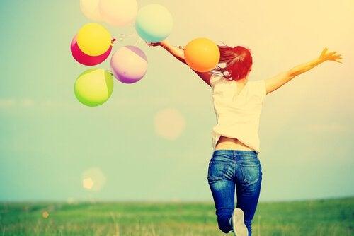 Mulher feliz segurando balões coloridos