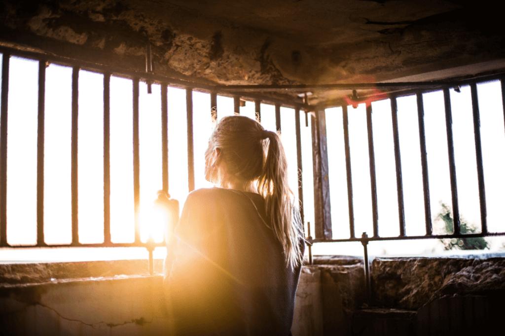 Mulher olhando por janela de grades