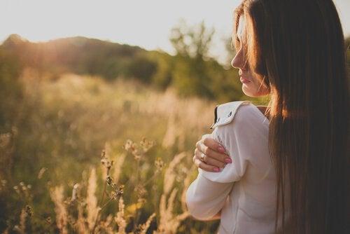 Mulher abraçando a si mesma no campo