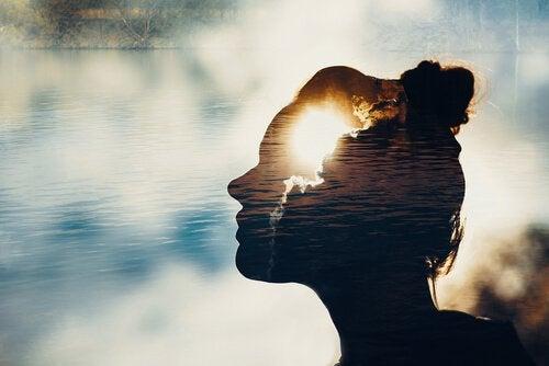 Sombra de mulher diante de lago
