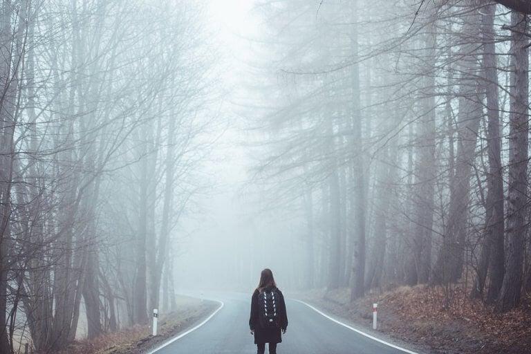 Mulher perdida em estrada com neblina